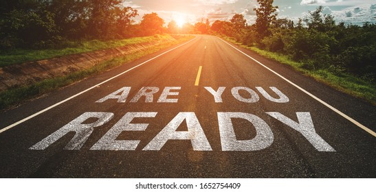Are you ready written on highway road in the middle of empty asphalt road at  beautiful blue sky.