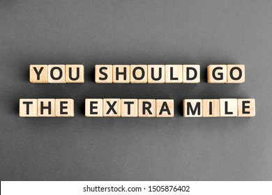 You should go the extra mile - phrase from wooden blocks with letters, to make a special effort try harder concept,  grey background
