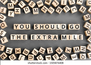 You should go the extra mile - phrase from wooden blocks with letters, to make a special effort try harder concept, random letters around, grey background