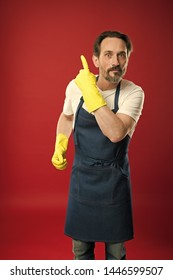 You should see it. Eldery household worker presenting something. Mature man pointing finger up. Senior man wearing bib apron and yellow rubber gloves. Providing household service.
