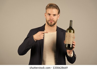 You should try this. Man holds bottle alcohol drink. Social and cultural aspects of drinking. Businessman formal suit confidently welcomes grey background. Man hospitable presenting bottle alcohol.