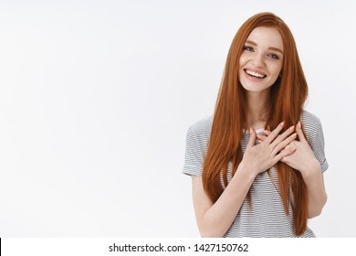 You stuck my heart. Charming lively tender feminine young redhead girl flirting look pleased laughing joyfully hold palms pressed chest heartwarming gesture touched, delighted sincerely smiling