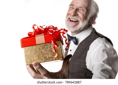 For you. Waist up portrait of joyful greybeard man holding beautiful box with red ribbon on top. Focus on present. Isolated on background