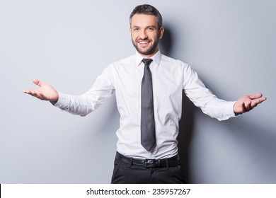 You are welcome! Cheerful mature man in shirt and tie gesturing welcome sign and smiling while standing against grey background
