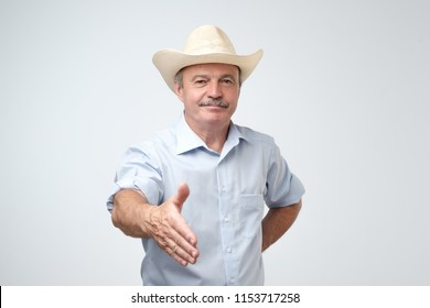 You are welcome concept. Cheerful mature man in blue shirt and cowboy hat gesturing welcome sign and smiling while standing against gray wall. He is happy to meet dear guests