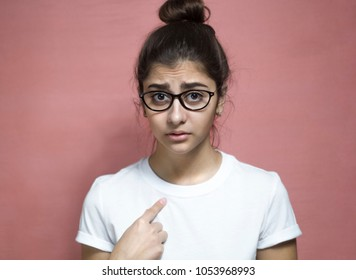You to me? Who am I? Portrait of a beautiful Indian girl in a white T-shirt and glasses, questioningly points at herself, an indeterminate facial expression.
