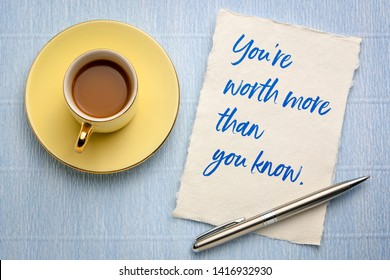 You are worth more than you know - handwriting on a piece of handmade rag paper with a cup of coffee