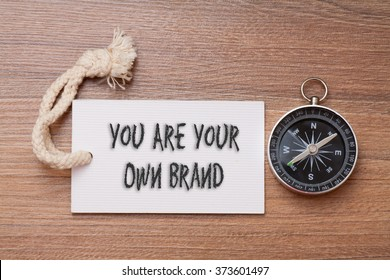 You are your own brand - business tips handwriting on label with compass