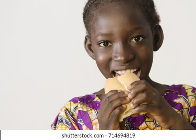 Youg African girl eating some bread - isolated on white
