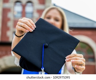 A youg lady is proudly showing her graduation cap.