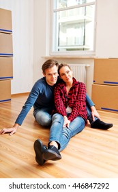 Yougn happy couple sitting on the floor in new house