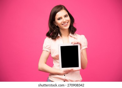 Yougn happy woman showing blank tablet computer screen over pink background