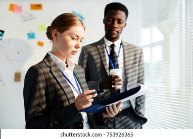 Youing female agent reading paper with important information with colleague near by