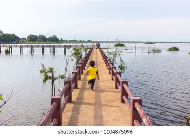 Youmg Male kid running at  public walk way at Talay Noi water market in Phatthalung, Thailand