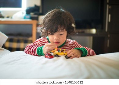 Youn Asian boy playing lego and toy cars on the bed.White sheet.Bedroom morning activity.School holiday season.Indoor activity.Preschooler and creative mind.Gifted child in home environment.
