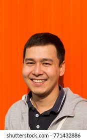 Youn Asian guy, boy different face emotions in portrait style on orange and white background. Expression, cheerful, serious, facial, fun, humor, laughing, crazy, smiling, surprise, mad, joy, sadness.