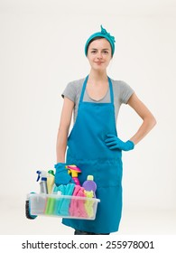 youn beautiful maid standing and holding cleaning supplies getting ready for work. isolated on white background