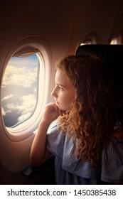Youn girl looks outside the window in plane