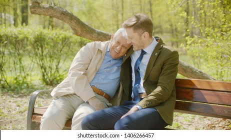 Youn man is hugging his old father on the bench in the autumn park