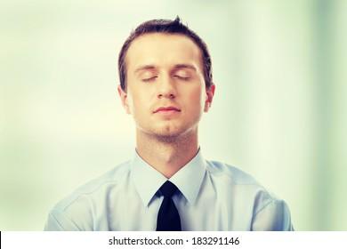 Yound caucasian business man meditating