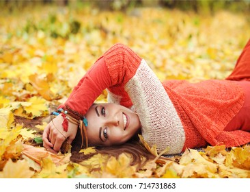 Yound cute woman have a rest lying in autumn park, looking at camera