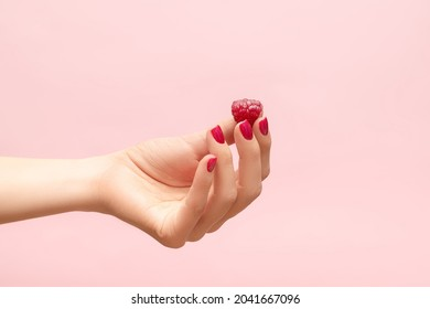 Yound female hand hold ripe red raspberry on a fingers. Female hand with raspberry isolated on pink background. Female hand with crimson manicure. Crimson nail design.