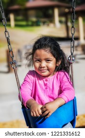 Yound latino girl sitting in a swing wearing a pink shirt with messy hair in an outdoor park.