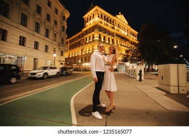 Yound man and woman walkin in the city at night. Evening Wiena. Building with lights