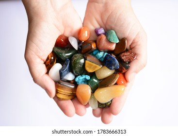 Yound woman is holding a collection of various raw mineral gemstones in her palm isolated on white background
