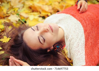 Yound woman relax with closed eyes lying in autumn park