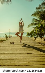Younf european woman standing in yoga tree pose - vrikshasana on the sea background in Thailand. Girl is meditating on the boardwalk near the beach.