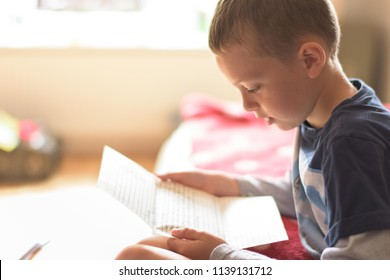 A young 10 year old boy with ADHD, Autism, Aspergers Syndrome reading a letter at home for a news article, written by pupils from his former school