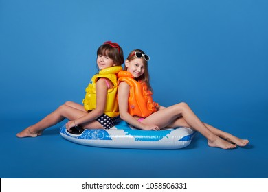 young 2 girls friends posing on inflatable mattress, life jacket. Summer concept rest beach, pool, resort,vacation,swimming. Happy children teenagers on blue isolated background, like seawater,studio.