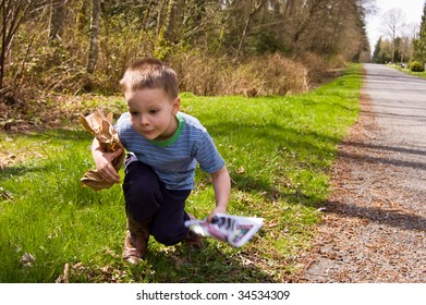 A young 4 year old Caucasian boy is picking up garbage on the side of the road to do his share for helping ecology and environmental issues.