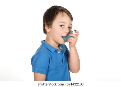 Young 5 years old boy using asthma blue reliever inhaler. Copy space. White background. Isolated.