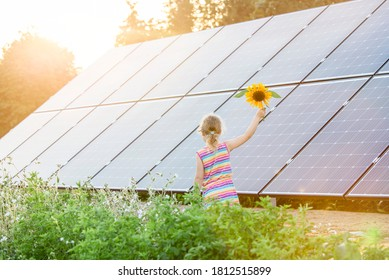 Young 6 year old blonde girl child standing in front of small solar panel farm in countryside. Renewable energy concept. Sun lens flare.