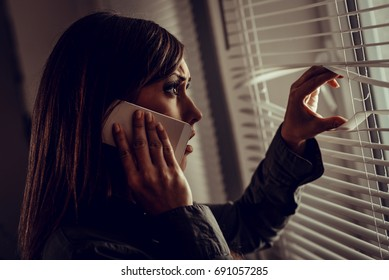 Young abused woman scared looking through the window seeking safety.