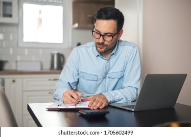 Young accountant working from home counting on calculator and writing in his notebook.
