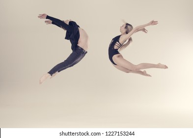 young acrobat sensual dancers on empty background