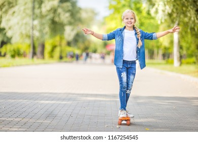 Young active beautiful stylish smiling girl balancing on a skateboard in a city park