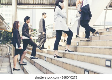 Young active business people walking up stair to go to work in modern city. Crowded group of people in big city lifestyle with briefcase, smart phone, cup of coffee. Business Lifestyle Concept.