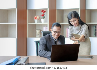 Young and active, enthusiastic Asian business man and woman talking and looking at notebook computer together in modern office. Team of businesspeople working together.