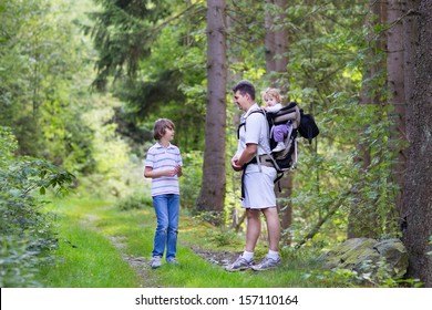 Young active father hiking with his school age son and baby daughter in a beautiful autumn forest