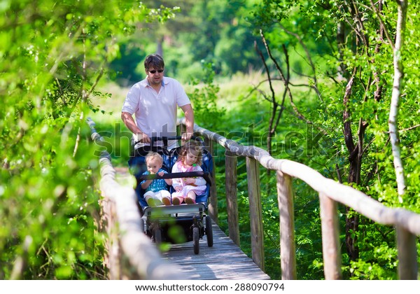 Young active father with kids in double stroller in a park. Dad with twin pram walking in the forest.  Parent with twins, son and daughter, hiking in the woods. Outdoor fun for family with children.
