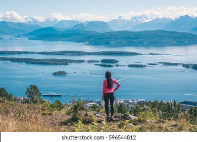 Young active female enjoying spectacular Varden - the Molde Panorama view over the norwegian fjord, mountains, islands and small town. View from the top of the rock.