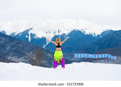 Young active girl stands on the top of mountain with ski suit taken off and hands wide open enjoy beautiful view