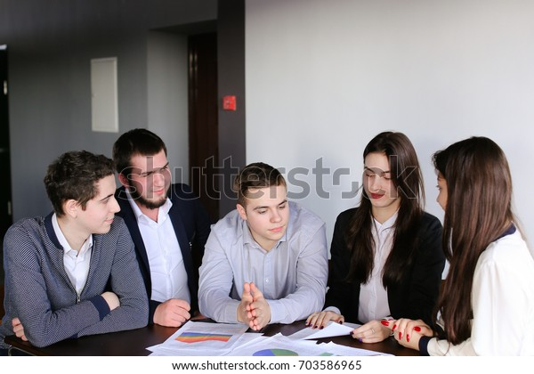 Young and active male and female administrators of company together read annual report and laugh with each other's smiles. Friendly company of professionals solves important issues and problems