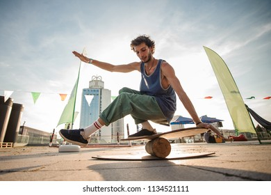 Young active man keeping balance on the wooden board against the background of city buildings on summer day