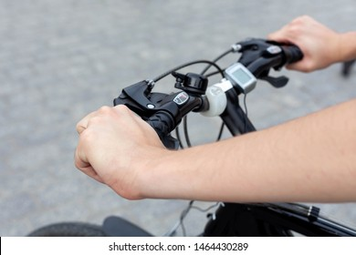 Young active man on a bike resting his hands on the handle bars, concrete background. Speedometer and led lighting equipment accessories shown. Outdoor cycling activity, urban biking trip concept