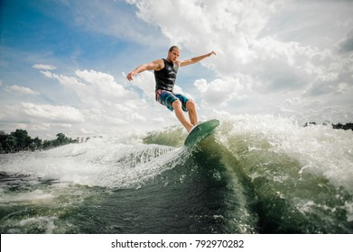 Young and active man wakesurfing on the board down the river against the background of sky